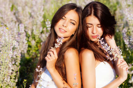 two smiling beautuful brunettes in the flowers  field