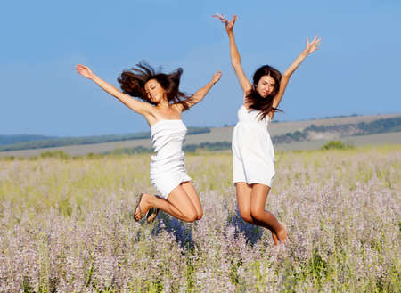 two smiling beautuful brunettes jumping in the flowers  field photo