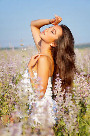 smiling beautuful brunette in the flowers  field