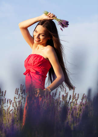 Beautiful long-haired brunette in a lavender field Stockfoto