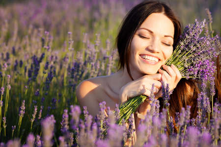 Beautiful long-haired brunette in a lavender field Фото со стока
