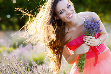 smiling woman: Beautiful long-haired brunette in a lavender field Stock Photo