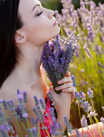 Beautiful long-haired brunette in a lavender field Stockfoto