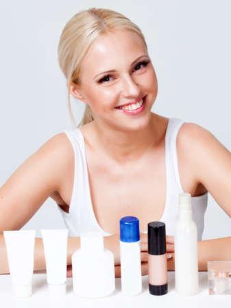 blonde met stralende huid in de buurt van de potjes van cosmetica Stockfoto