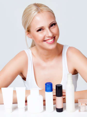 blonde with radiant skin near the jars of cosmetics