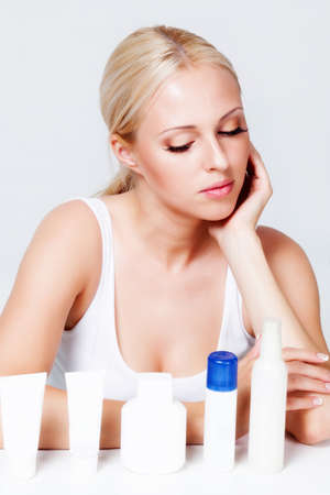 soft skin: blonde with radiant skin near the jars of cosmetics