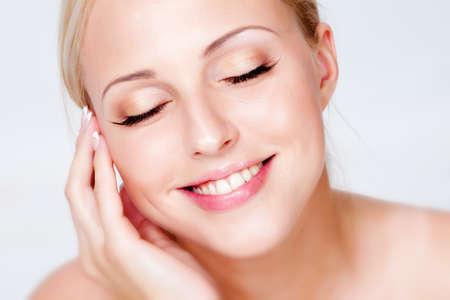 Portret van blonde met de ideale huid, geïsoleerd op een witte achtergrond