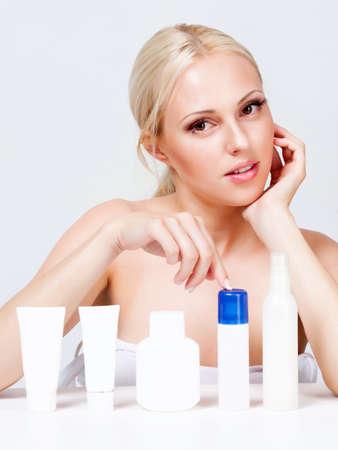 blonde met stralende huid in de buurt van de potten van cosmetica