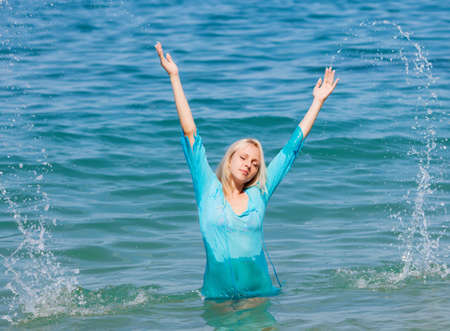 beautiful blonde in a blue dress standing in the sea photo