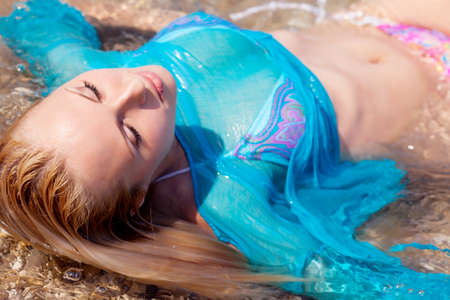 wet woman: beautiful blonde in a blue dress floating in the sea