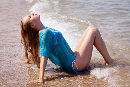 beautiful blonde in a blue dress floating in the sea photo