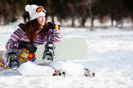 Girl with snowboard sitting on the snow photo