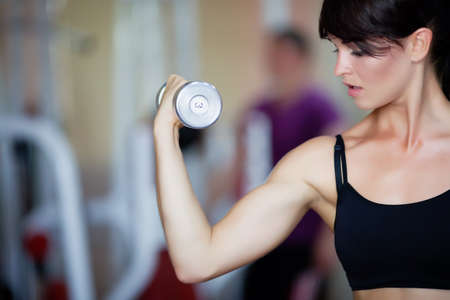 Girl holding dumbbells in hands photo