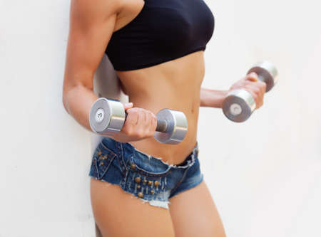 Girl holding dumbbells in hands