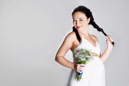 Pregnant woman in studio with flowers Banco de Imagens - 15059713