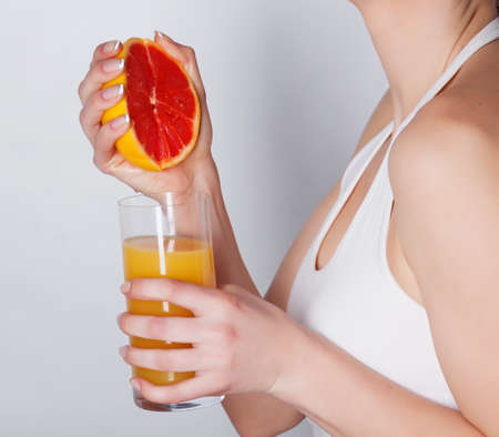 squeezing: Girl squeeze grapefruit juice Stock Photo
