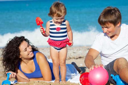 小さな女の子が、ビーチで遊んでと家族