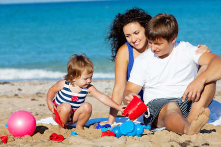 Family with little girl playing on the beach photo