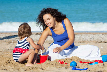 Family with little girl playing on the beach Imagens