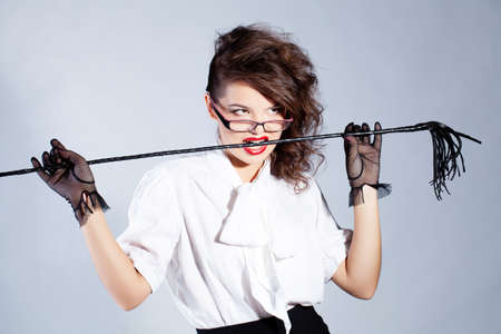 Strict teacher with glasses and a whip
