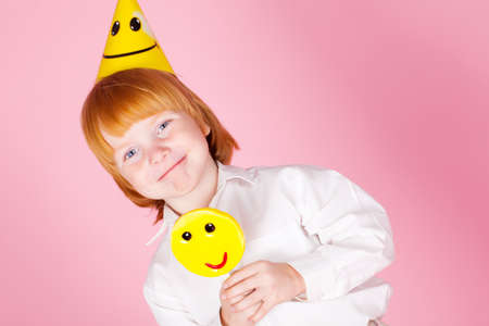 Red hair boy with candy in studio photo