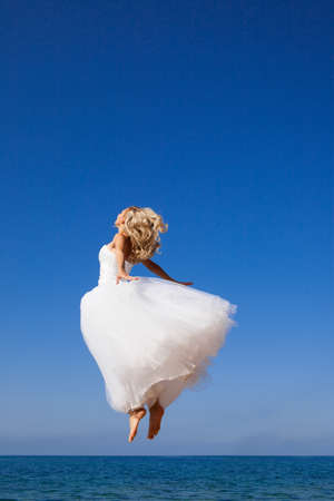 Beautiful bride jumping over the sea