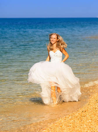 Beautiful bride running on the beach photo