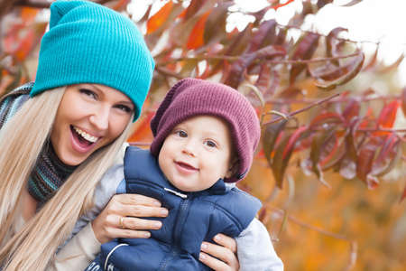 blonde mom: Mother with son in autumn peach garden Stock Photo