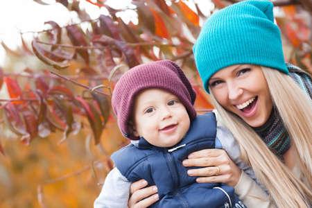 Mother with son in autumn peach garden Standard-Bild