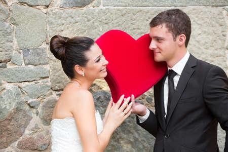 Bride and groom outdoor portrait with red heart