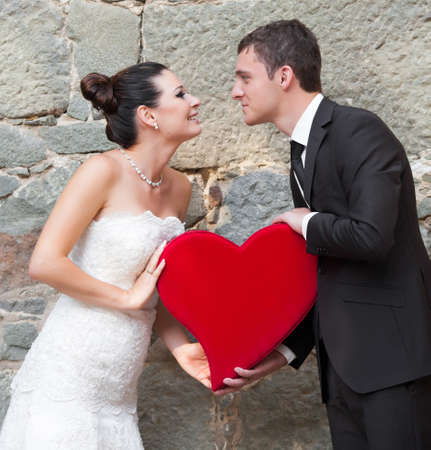 Bride and groom outdoor portrait with red heart photo