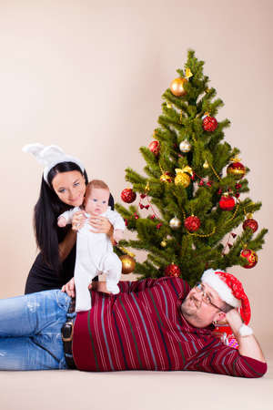 Happy family sitting near christmas pine Stock Photo - 16763657