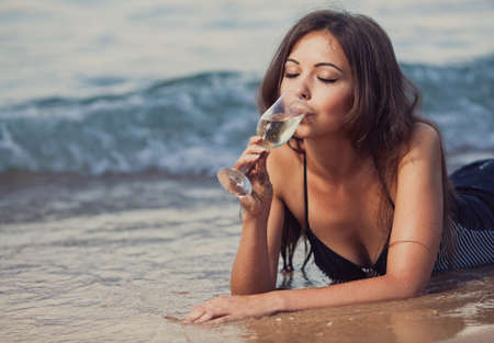 bikini sexy: Young girl with a glass of champagne on the beach