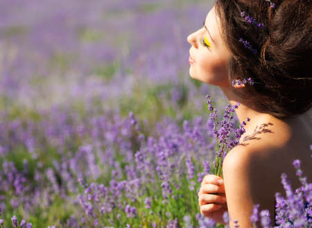Beautiful girl on the lavender field Фото со стока