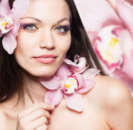 Beautiful brunette girl with orchid flowers in hair photo