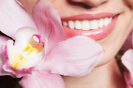Beautiful girl smile with orchid flower photo
