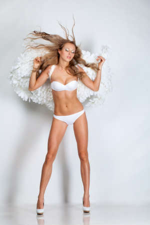 Beautiful blond girl with white wings photo
