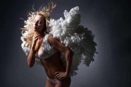 黒い背景に白い翼を持つ美しいブロンドの女の子 写真素材