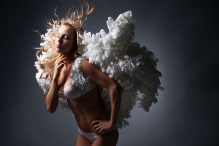 Beautiful blond girl with white wings on black background