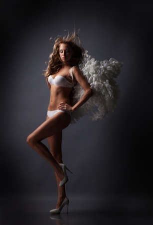 Beautiful blond girl with white wings on black background photo