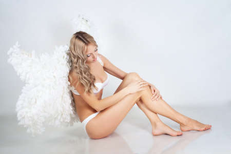 Beautiful blond girl with white wings sitting on the floor photo