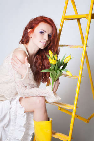 gumboots: Beautiful girl in yellow gumboots near ladder Stock Photo