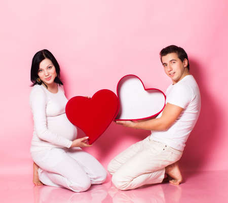 Pregnancy young woman with man in studio  photo
