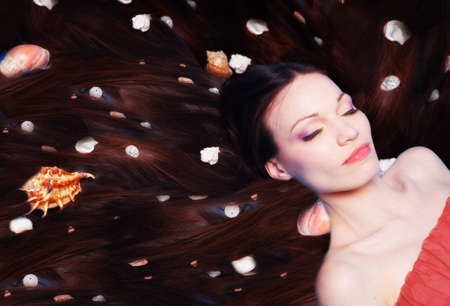 Beautiful woman with sea shells in long hair photo