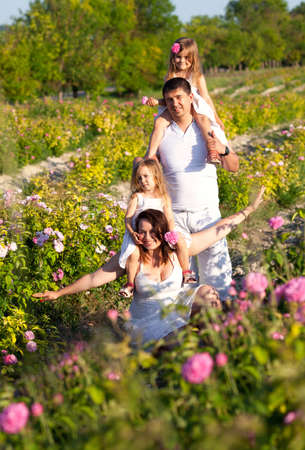 Happy family in blossom rose garden photo