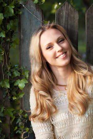 Beautiful blond woman portrait near wooden fence photo