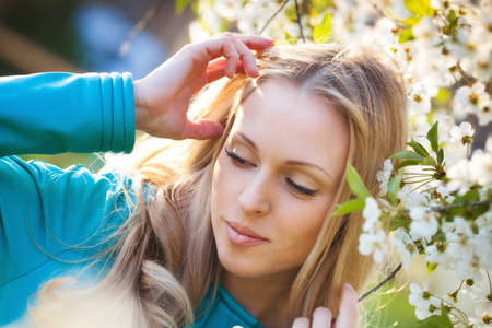 Beautiful blond woman portrait near cherry blossom tree photo