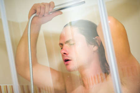 douche: Young man having douche in bathroom Stock Photo