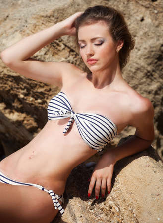 Young woman lying on the stone in swimsuit photo