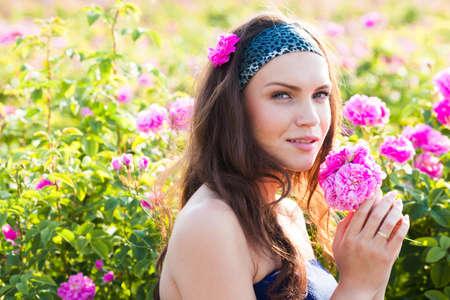 Beautiful young woman in rose garden photo